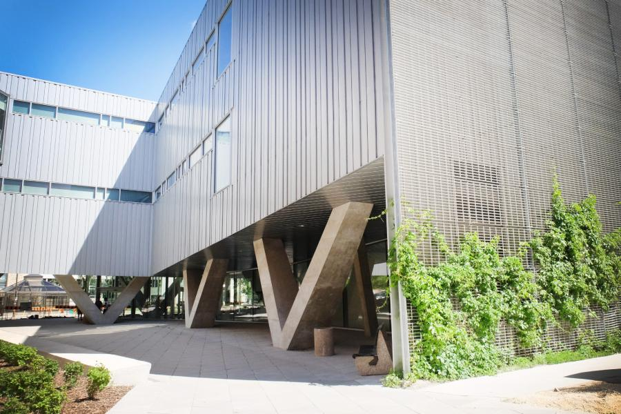 Exterior view of the ArtLab with its unique V shaped cement pillars and vines growing up the aluminum living wall.