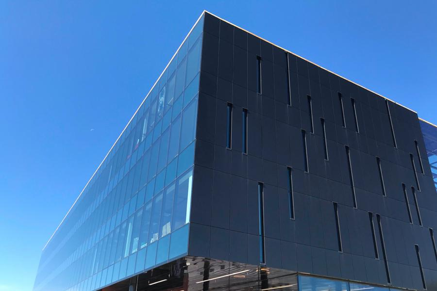 The dark rectangular glass exterior of the Innovation Hub building captures the reflection of the bright blue sky.